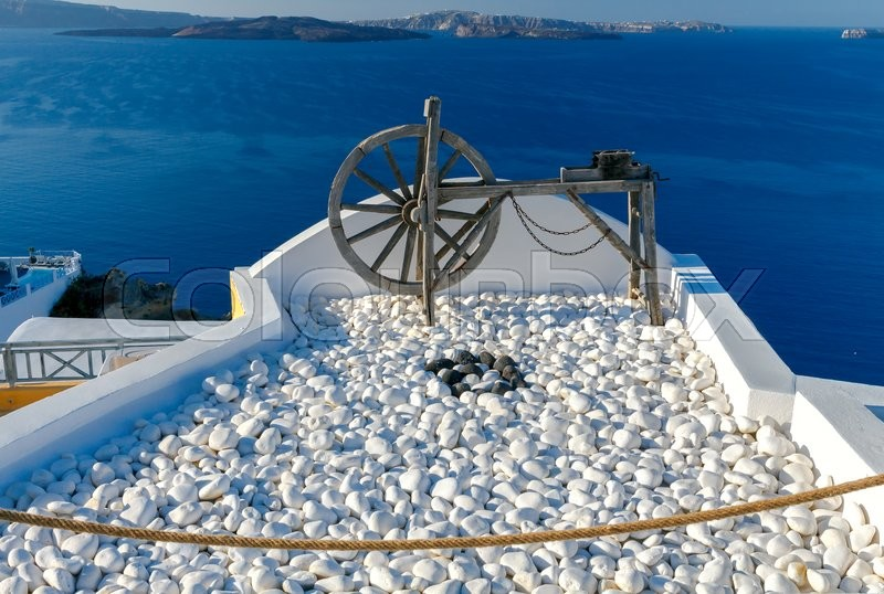 Stock image of 'Rotating wooden wheel in the village of Oia. Santorini Island. Greece.'