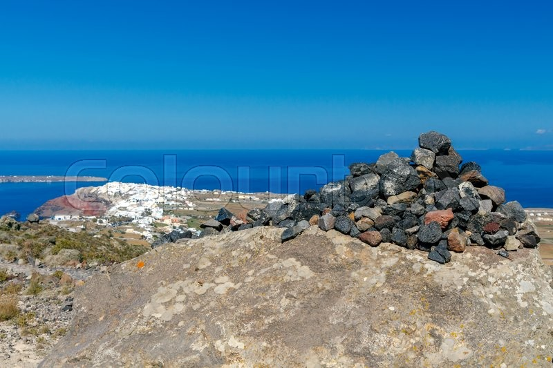 Stock image of 'A small pyramid of volcanic rocks on the background of the village  Oia on Santorini Island.'
