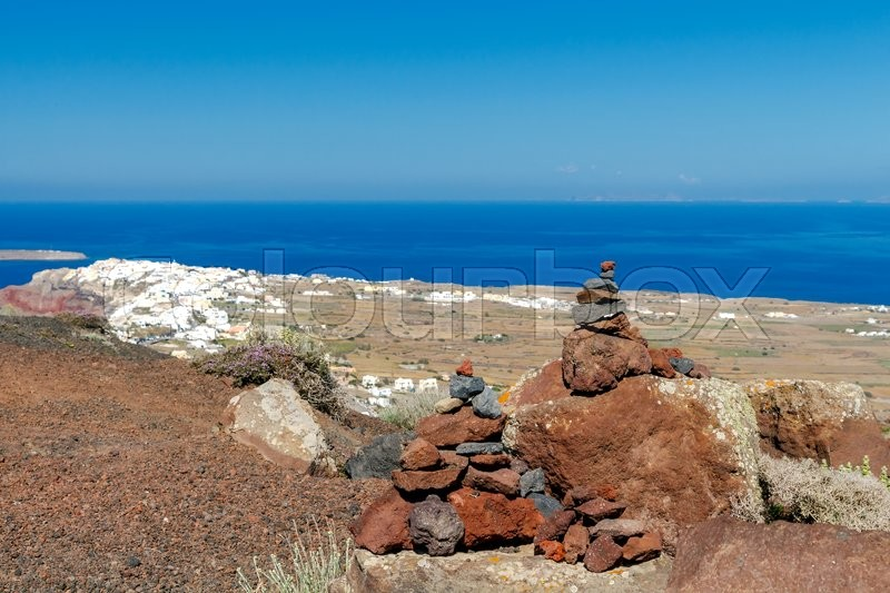 Stock image of 'A small pyramid of volcanic rocks on the background of the village of Oia on Santorini Island.'