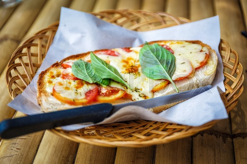 Stock image of 'Italian bruschetta with tomatoes, basil and cheese on grilled crusty bread'