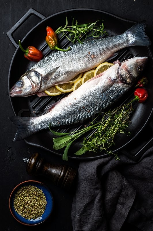 Stock image of 'Raw uncooked seabass fish with herbs and spices in cast iron cooking pan on black wooden background. Top view, dark consept'