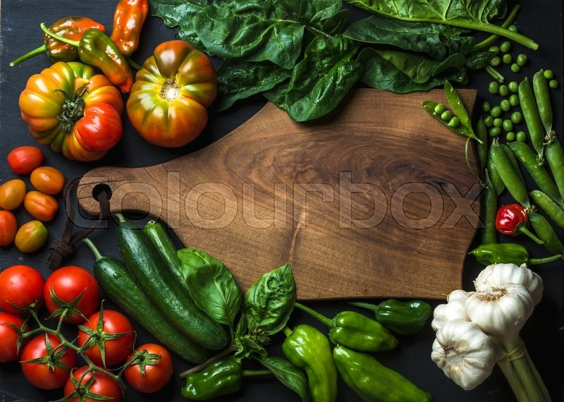 Stock image of 'Fresh raw vegetable ingredients for healthy cooking or salad making with dark wooden cutting baoard in center, top view, copy space. Diet or vegetarian food concept, horizontal composition'