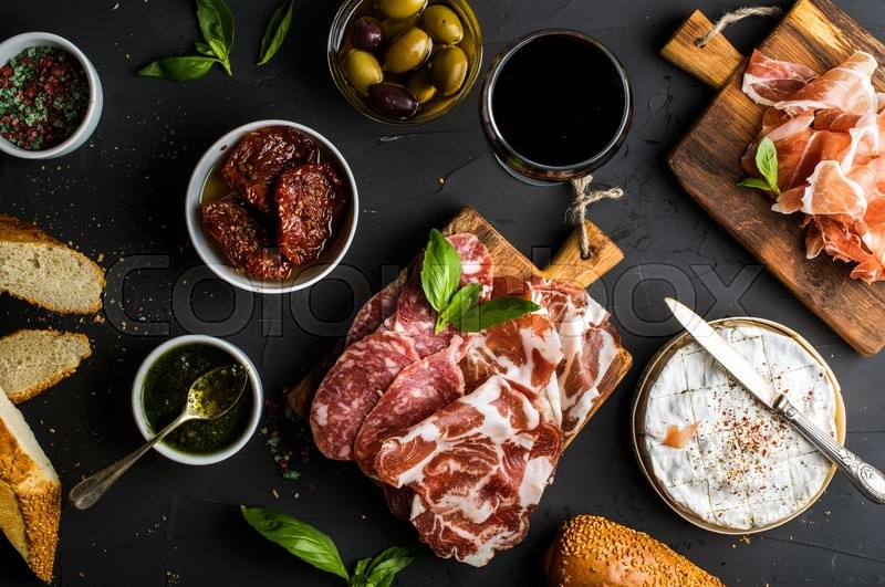 Stock image of 'Wine snack set. Glass of red, meat selection, mediterranean olives, sun-dried tomatoes, baguette slices, camembert cheese and spices on black background, top view'
