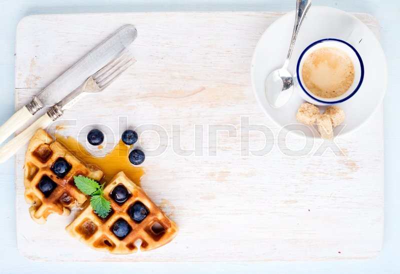 Stock image of 'Espresso coffee cup and soft belgian waffles with fresh blueberries and marple syrup on white painted wooden board over light blue background. Top view, copy space, horizontal'