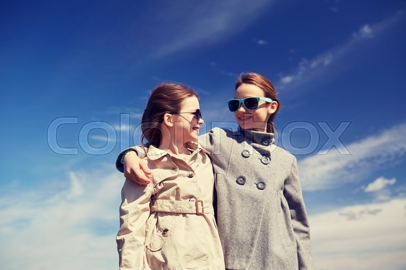Stock image of 'people, children, friends and friendship concept - happy little girls in sunglasses hugging and talking outdoors'