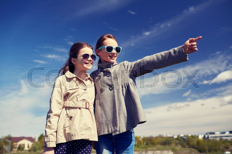 Stock image of 'people, children, friends and friendship concept -happy little girls in sunglasses hugging and pointing finger outdoors'
