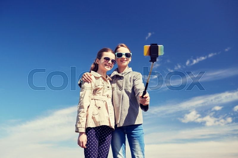 Stock image of 'people, children, friends and friendsip concept - happy girls taking picture with smartphone on selfie stick outdoors'