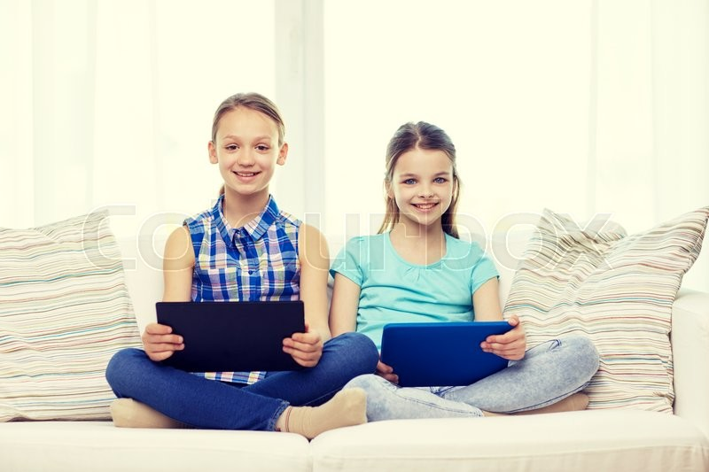 Stock image of 'people, children, technology, friends and friendship concept - happy little girls with tablet pc computers sitting on sofa at home'