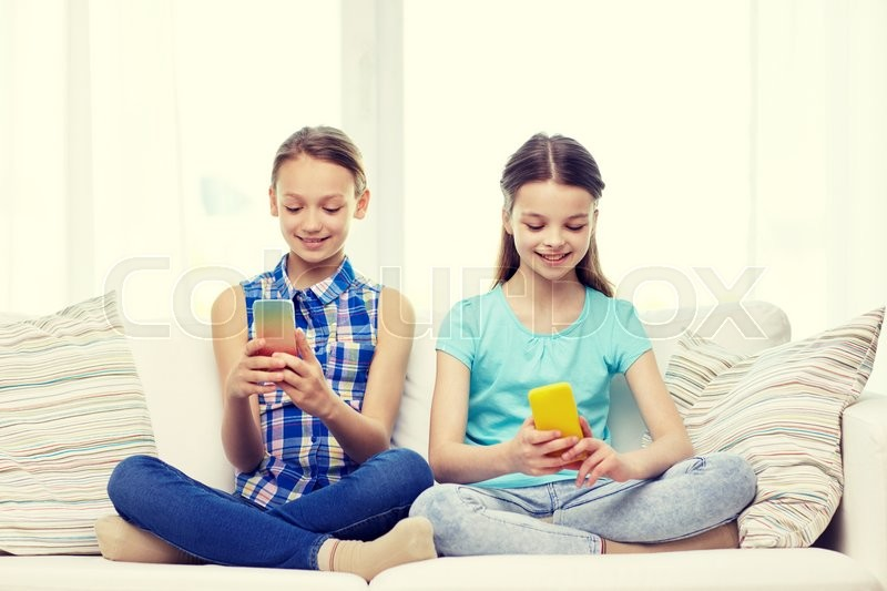 Stock image of 'people, children, technology, friends and friendship concept - happy little girls with smartphones sitting on sofa at home'