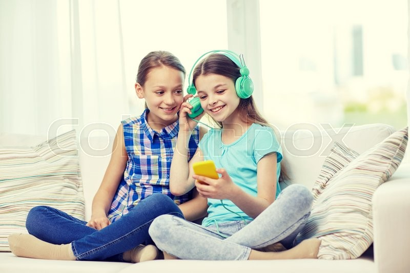 Stock image of 'people, children, technology, friends and friendship concept - happy little girls with smartphone and earphones sitting on sofa and listening to music at home'