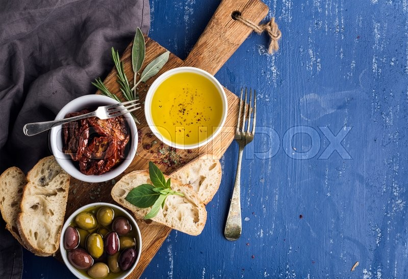 Mediterranean snacks set. Olives, oil, herbs and sliced ciabatta bread on yellow rustic oak board over painted dark blue background, top view, copy space, stock photo