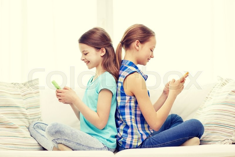 Stock image of 'people, children, technology, friends and friendship concept - happy little girls with smartphones sitting on sofa back to back at home'