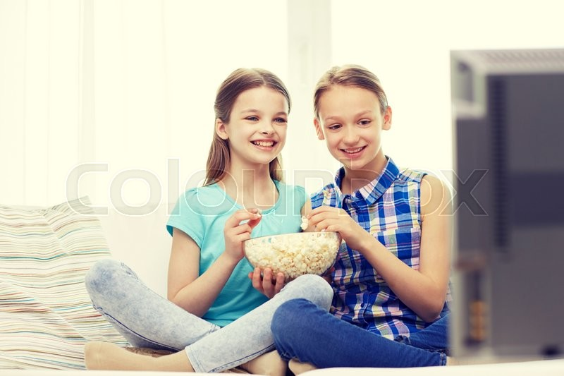 Stock image of 'people, children, television, friends and friendship concept - two happy little girls watching comedy movie on tv and eating popcorn at home'