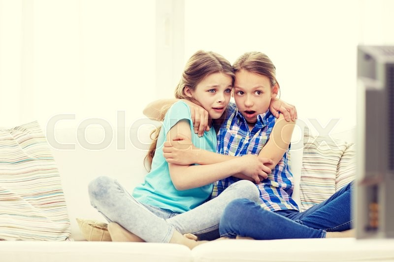 Stock image of 'people, children, television, friends and friendship concept - two scared little girls watching horror on tv at home'