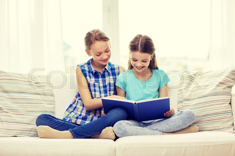 Stock image of 'people, children, friends, literature and friendship concept - two happy girls sitting on sofa and reading book at home'