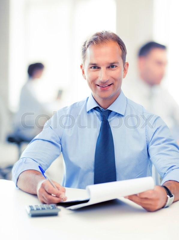 Stock image of 'middle-aged businessman with notebook and calculator in office'