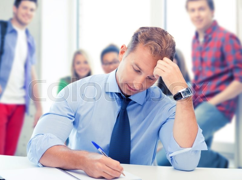 Stock image of 'picture of handsome teacher writing in notebook'