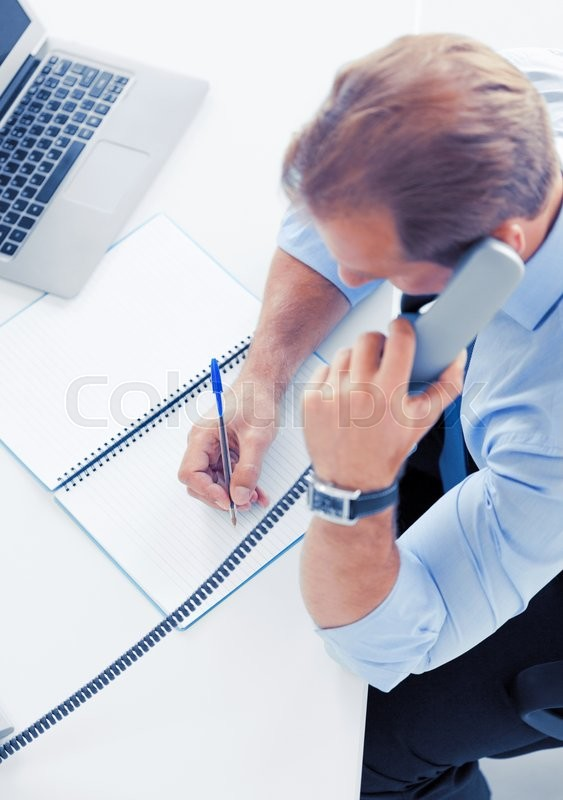 Stock image of 'business, office, school and education concept - businessman talking on the phone'