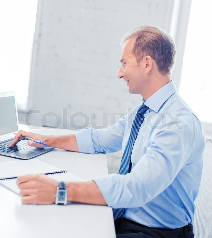 Stock image of 'business, office, school and education concept - smiling businessman working in office'