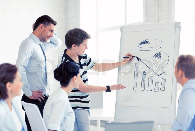 Stock image of 'smiling business team working with flipchart in office'