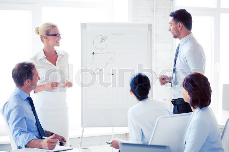Stock image of 'smiling business team working with flip chart in office'