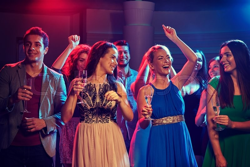 Stock image of 'party, holidays, celebration, nightlife and people concept - happy friends with glasses of champagne dancing in club'