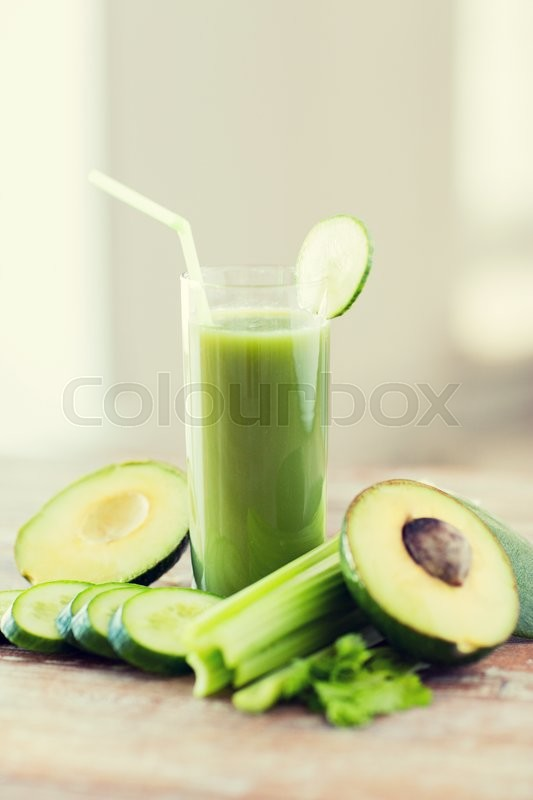Stock image of 'healthy eating, organic food and diet concept - close up of fresh green juice glass and vegetables on table'
