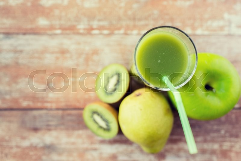 Stock image of 'healthy eating, organic food and diet concept - close up of fresh green juice glass and fruits on table'