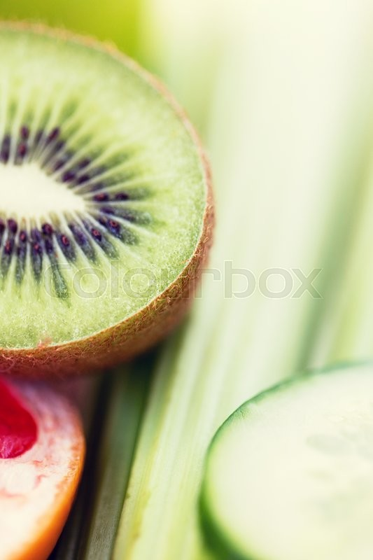 Stock image of 'diet, vegetable food, healthy eating and objects concept - close up of ripe kiwi and cucumber slices'