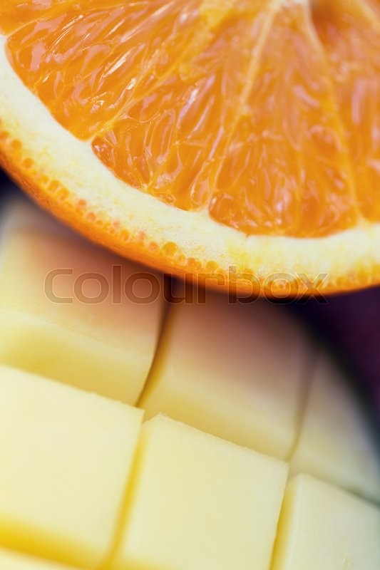 Stock image of 'healthy eating, food, fruits and diet concept - close up of fresh juicy orange and mango slices'
