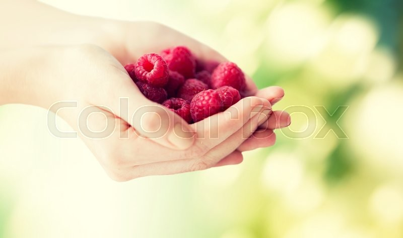 Stock image of 'healthy eating, dieting, vegetarian food and people concept - close up of woman hands holding raspberries over green natural background'