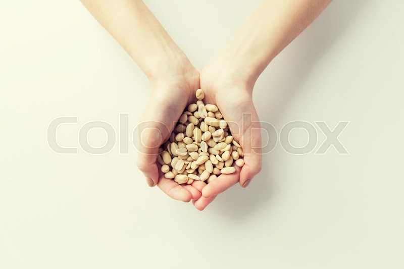 Stock image of 'healthy eating, dieting, vegetarian food and people concept - close up of woman hands holding peeled peanuts at home'