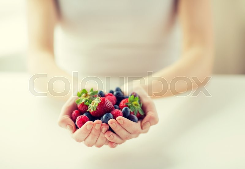 Stock image of 'healthy eating, dieting, vegetarian food and people concept - close up of woman hands holding berries at home'