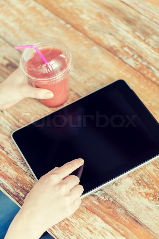 Stock image of 'healthy eating, diet, technology and people concept - close up of woman hands with cup of smoothie pointing finger to tablet pc computer black blank screen on wooden table'