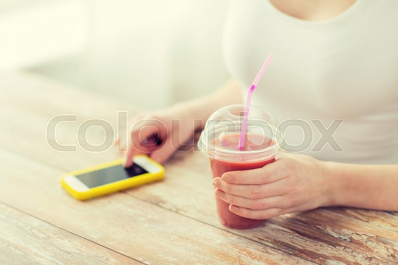 Stock image of 'healthy eating, diet, technology and people concept - close up of woman with smartphone and cup of smoothie sitting at table'