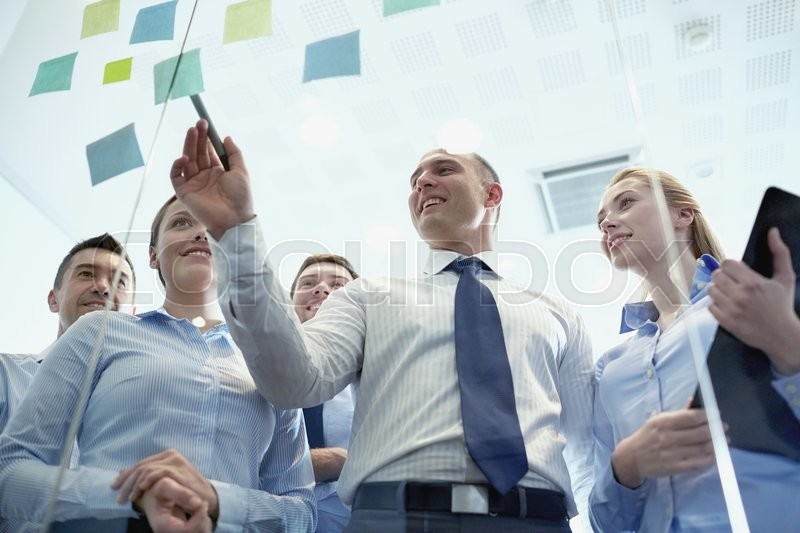Stock image of 'business, people, teamwork and planning concept - smiling business team with marker and stickers working in office'