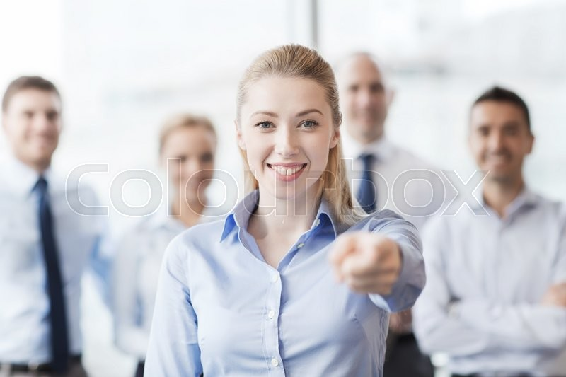 Stock image of 'business, people and teamwork concept - smiling businesswoman pointing finger on you with group of businesspeople in office'