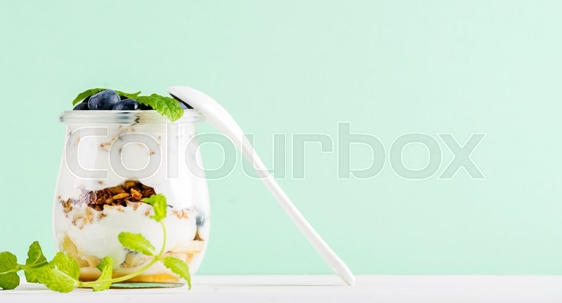Stock image of 'Yogurt oat granola with jam, blueberries and green leaves in glass jar on pastel mint backdrop, copy space'