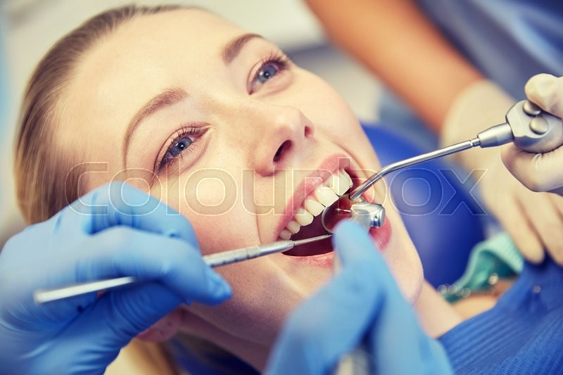 Stock image of 'people, medicine, stomatology and health care concept - close up of dentists and assistant with mirror, drill and dental air water gun spray treating female patient teeth at dental clinic'