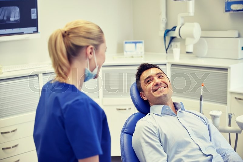 Stock image of 'people, medicine, stomatology and health care concept - happy female dentist with man patient talking at dental clinic office'
