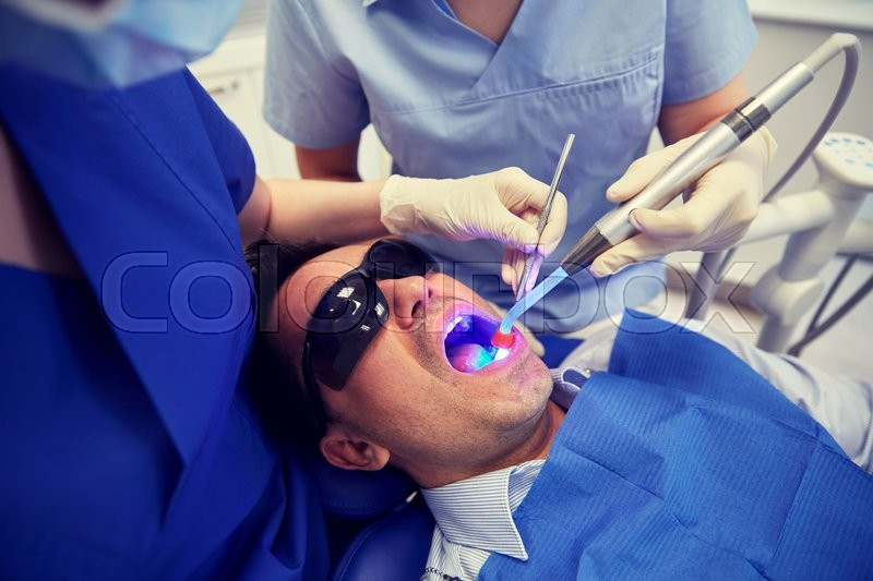 Stock image of 'people, medicine, stomatology and health care concept - female dentist and assistant with dental curing light and mirror treating male patient teeth at dental clinic office'