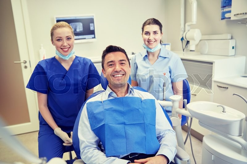 Stock image of 'people, medicine, stomatology and health care concept - happy female dentists with man patient at dental clinic office'