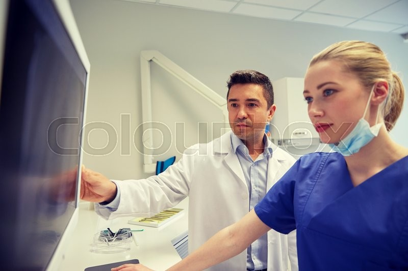 Stock image of 'people, medicine, stomatology, technology and health care concept - dentists looking to x-ray scan on monitor at dental clinic'