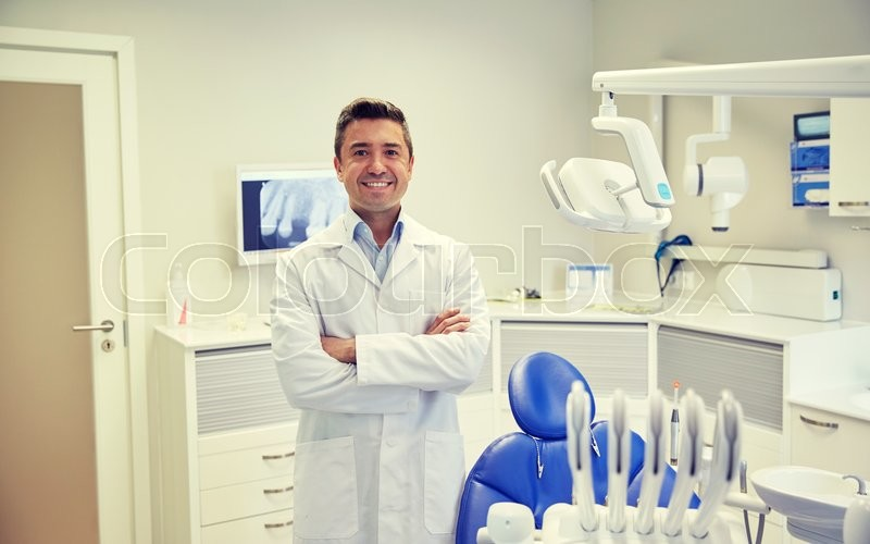 Stock image of 'people, medicine, stomatology and healthcare concept - happy middle aged male dentist in white coat at dental clinic office'