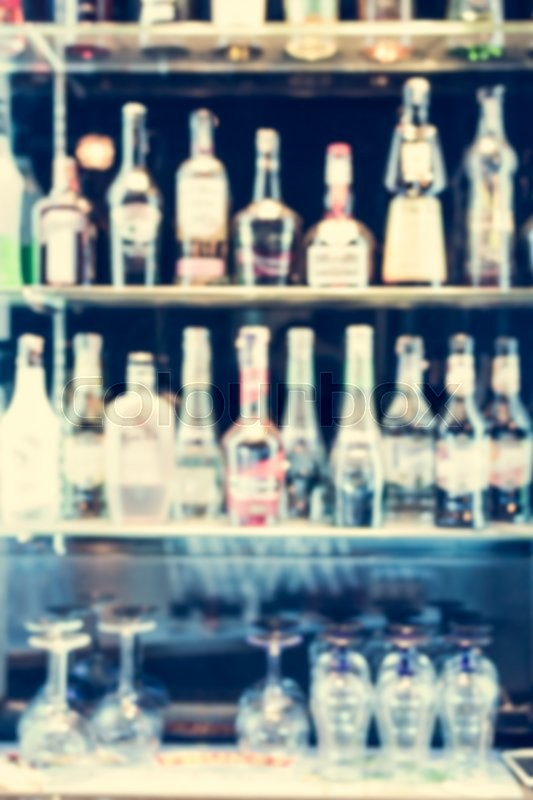 Stock image of 'Blurred bottle of alcoholic drinks and glasses are on the shelf for background'