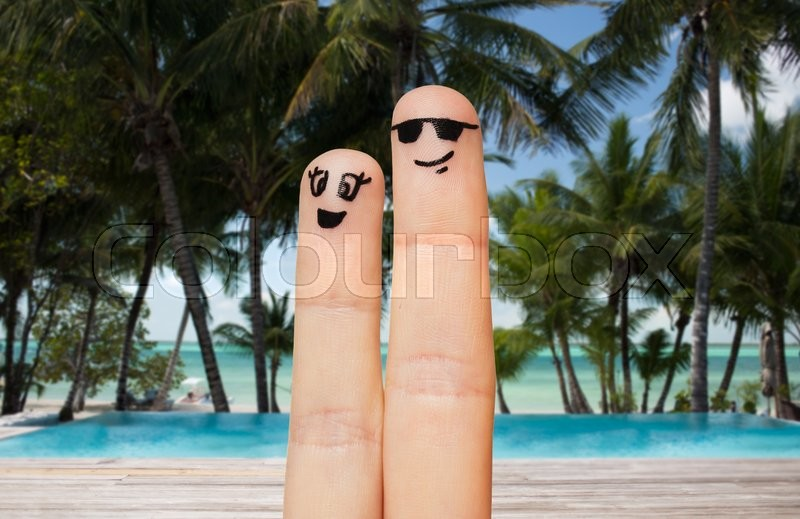 Stock image of 'family, travel, summer holidays, tourism and body parts concept - close up of two fingers with smiley faces over exotic tropical beach with palm trees and pool background'