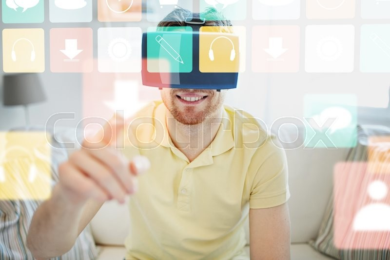 Stock image of 'technology, gaming, media, entertainment and people concept - happy young man in virtual reality headset or 3d glasses with computer icons at home'