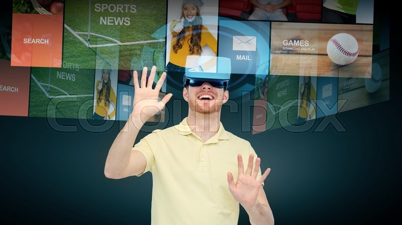 Stock image of '3d technology, virtual reality, cyberspace, entertainment and people concept - happy young man with virtual reality headset or 3d glasses networking over black background'