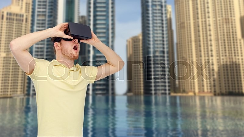 Stock image of '3d technology, virtual reality, entertainment and people concept - happy young man with virtual reality headset or 3d glasses playing game over dubai city infinity edge pool background'