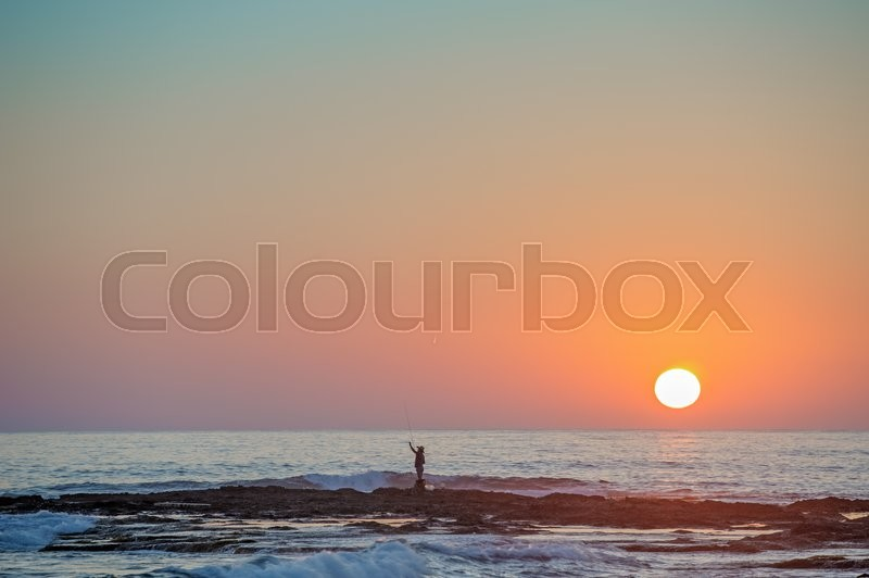 Stock image of 'Fisherman's silhouette on seashore at sunset'
